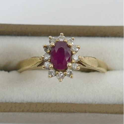 245 - A 9 carat gold ruby and diamond oval cluster ring, with import marks for London 1977, finger size O ...