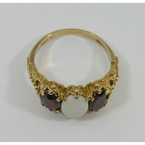 247 - A 9 carat gold Victorian style opal and garnet three stone ring, London 1975, the oval cabochon opal...