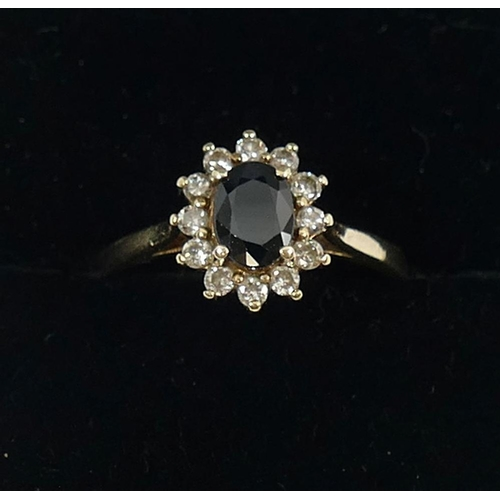 251 - A 9 carat gold dark sapphire and diamond oval cluster ring, with import marks for London 1987, the o...