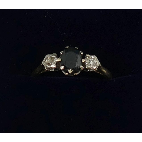 253 - An 18 carat gold sapphire and diamond three stone ring, Birmingham 1972, the dark oval mixed cut sap...