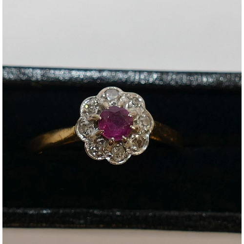 259 - A ruby and diamond circular daisy head cluster ring, the circular mixed cut ruby within eight small ...