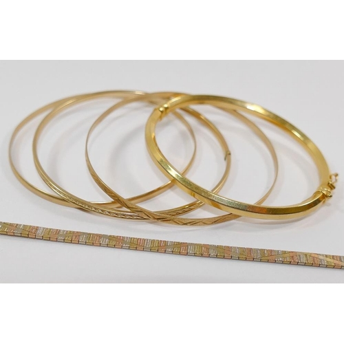 262 - Two circular 9 carat gold bangles, combined weight 8.4g, an unmarked yellow metal circular bangle, 3...