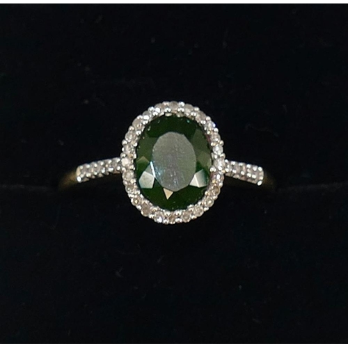 273 - A 9 carat gold chrome diopside and diamond oval cluster ring, Birmingham 2001, the bright green oval...