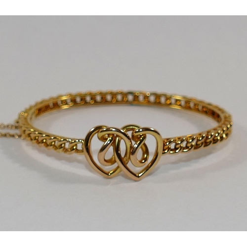 293 - A Victorian gold hinged bangle, of interwoven heart and curb link design, the clasp stamped '15', 14...