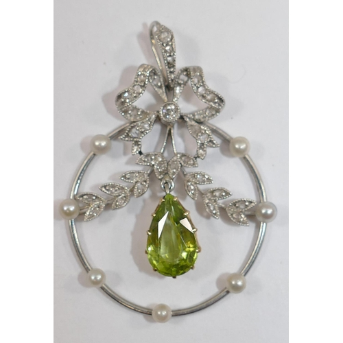 297 - An Edwardian diamond and peridot openwork pendant in the form of a ribbon and swags, with pear shape...
