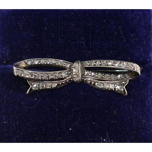 299 - A 19th century diamond bow brooch, set with small rose cut diamonds, 3.8cm wide...