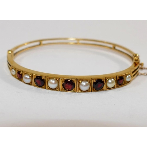 305 - A 9 carat gold Victorian style hinged bangle set with half pearls and garnets, London 1971,  13.6g g...