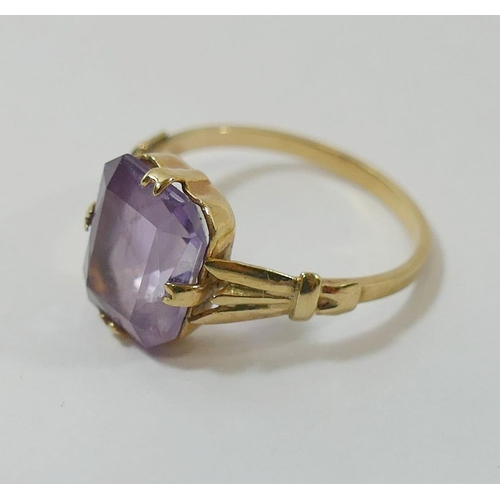 313 - A yellow metal amethyst single stone ring, the emerald-cut amethyst in claw setting to three section...