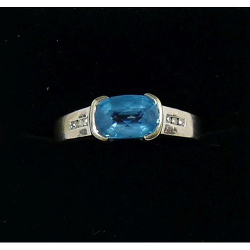 318 - A 14 carat white gold blue topaz and diamond ring, the cushion-shaped topaz in rub-over setting, fla...