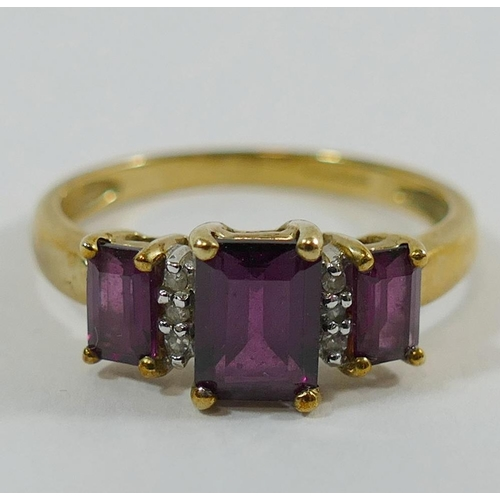 320 - A 9 carat gold almandine garnet three stone ring, the gallery set on either side with a small eight-...