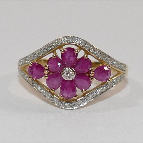 322 - A 9 carat gold ruby and diamond dress ring, the flower head design within open surround and diamond ...
