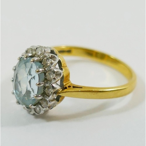 323 - An 18 carat gold diamond and aquamarine oval cluster ring, the oval mixed cut aquamarine in claw set...