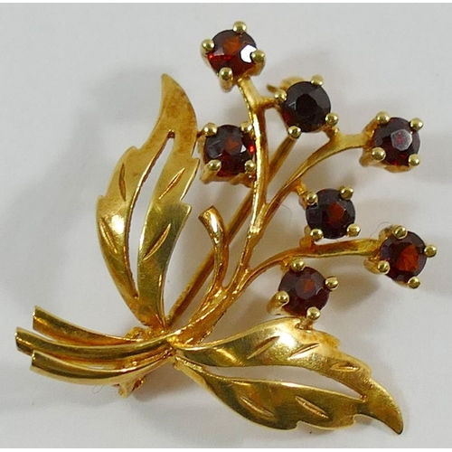 327 - A 9 carat gold floral spray garnet set brooch, the seven round mixed cut garnets in claw settings, 2...