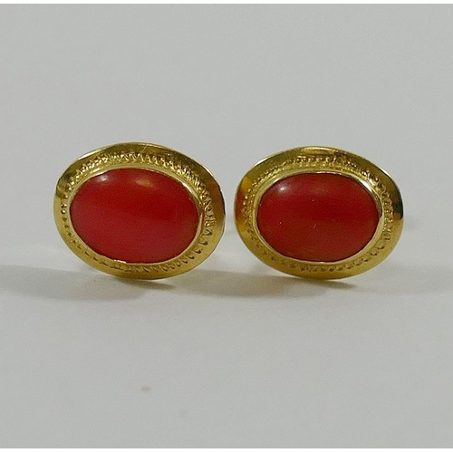 329 - A pair of yellow metal and coral oval stud earrings, indistinctly marked, 1.5g gross...