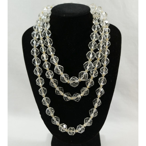 333 - A long facetted rock crystal bead necklace, the graduated beads individually knotted, 126cm long, a ...
