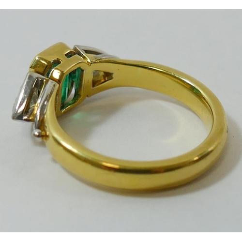 346 - An 18 carat gold emerald and diamond three stone ring by Nick Kellett, London 1997, the emerald-cut ...