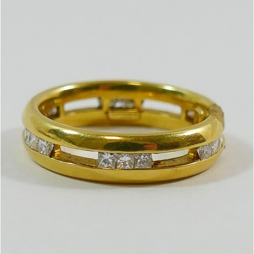 348 - An 18 carat gold and diamond eternity space ring by Nick Kellett, London 1998, the 18 princess cut d...