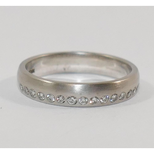 349 - An 18 carat brushed white gold wedding band, London 2010, by Nick Kellett set with a a band of 16 sm...