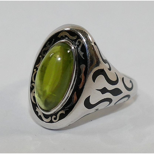 350 - An 18 carat white gold, black enamel and peridot 'tattoo' ring, London 2008, by Nick Kellett, the ov...