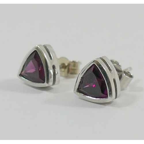 358 - A pair of 18 carat white gold rhondalite stud earrings, by Nick Kellett, the trilliant cut garnets i...