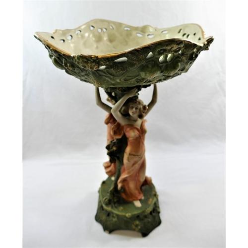 36 - A Royal Vienna Art Nouveau porcelain figural comport, modelled as two maidens holding aloft a basket...