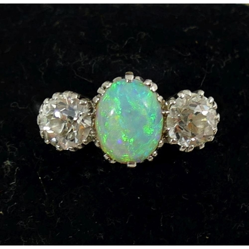 364 - An early 20th century opal and diamond three stone ring, the oval opal cabochon set between two old ...
