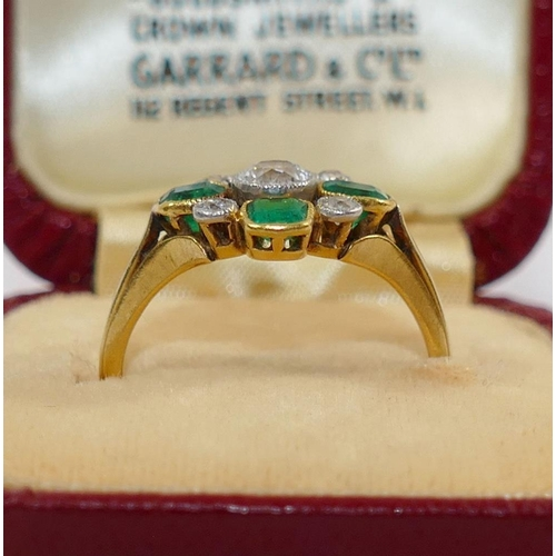 365 - An early 20th century emerald and diamond cluster ring, the central old cut diamond approximately 0....