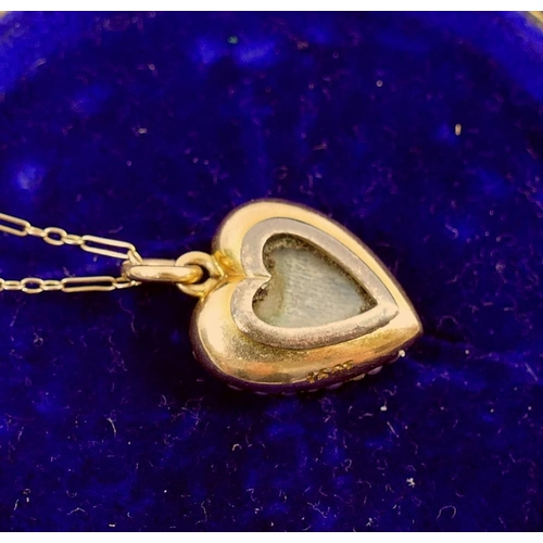 371 - A heart-shaped half seed pearl set pendant on chain, the pendant stamped '15CT', 1.8mm long, with gl...