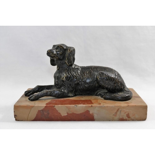 52 - A 20th century patinated bronze figure of a spaniel lying down, with ears cocked, on rectangular mar...