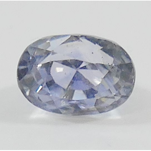 384 - An unset oval pale mixed cut sapphire, the loose stone measuring approximately 10mm long, 7mm wide a...
