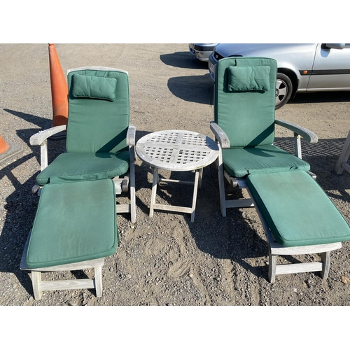 43 - A pair of teak steamer chairs together with a matching circular table and cushions...