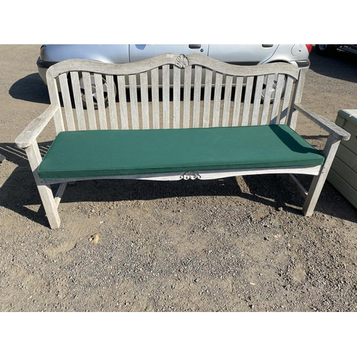 44 - A teak garden bench with upholstered green coloured cushion...