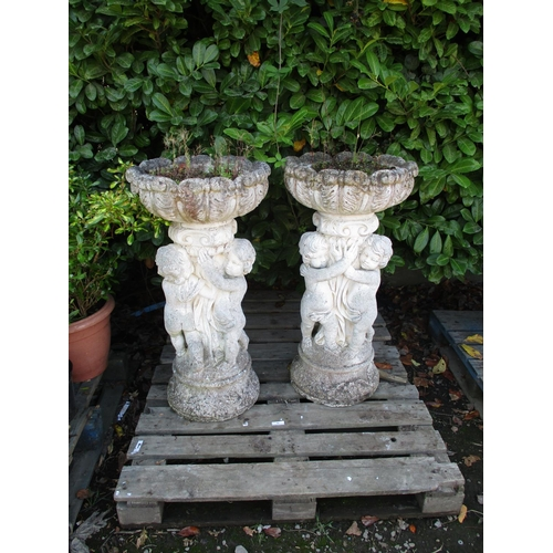 56 - A pair of reconstituted stone garden planters the pedestals modelled in the form of cherubs