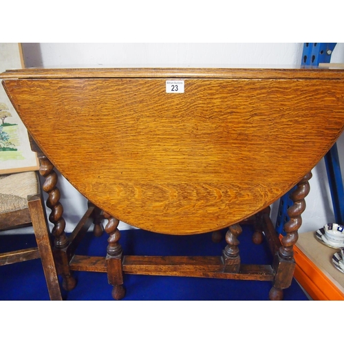 23 - Small drop leaf oval wooden table with barley twist legs...