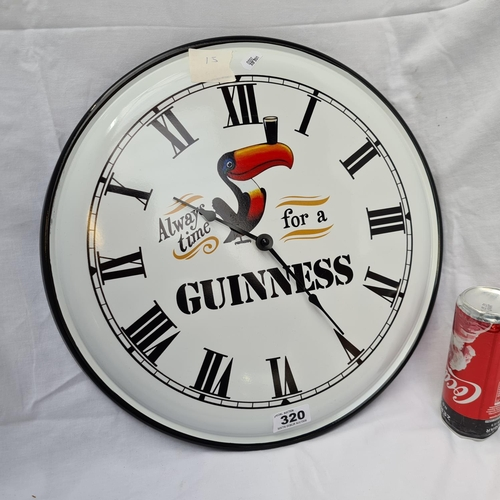 320 - Large, metal Guinness kitchen clock.