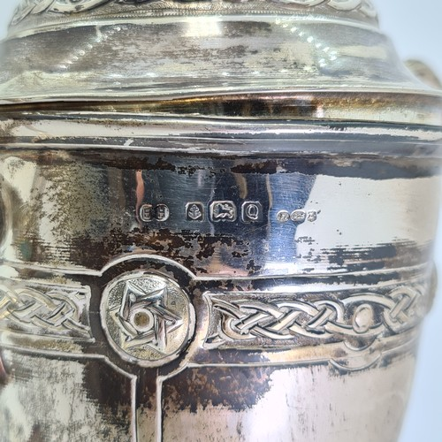 9 - A sterling silver presentation cup with celtic style band to lid and body. Standing on an ebonised b...