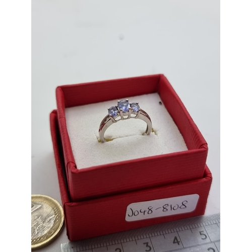 458 - A three stone 9 carat white gold tanzanite ring with diamond set shoulder mount. Weight 2.1g, size H...