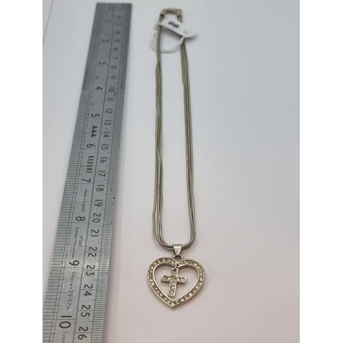12 - A sterling silver three strand heart shaped gem stone pendant, incorporating a cross. Total weight 1...