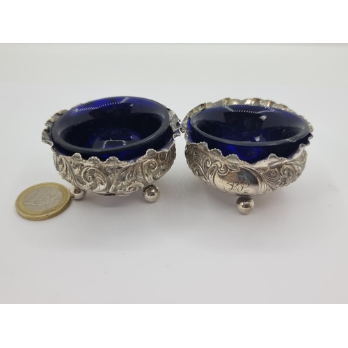 15 - A very pretty and interesting pair of sterling silver salt cruets, together with Bristol blue liners...