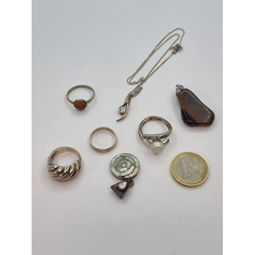 24 - A collection of five sterling silver rings, together with a tiger's eye pendant and a zircon stone p...