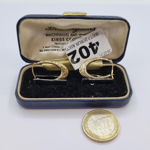 A pair of nine carat gold hoop earrings, suitable for pierced ears, in retailer's presentation case.