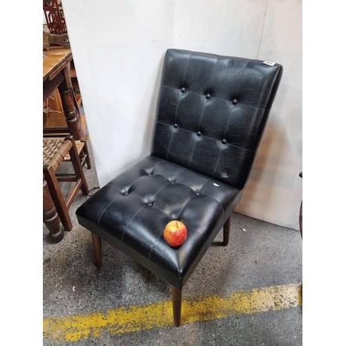 Mid century leather, button back chair, with tapered legs.