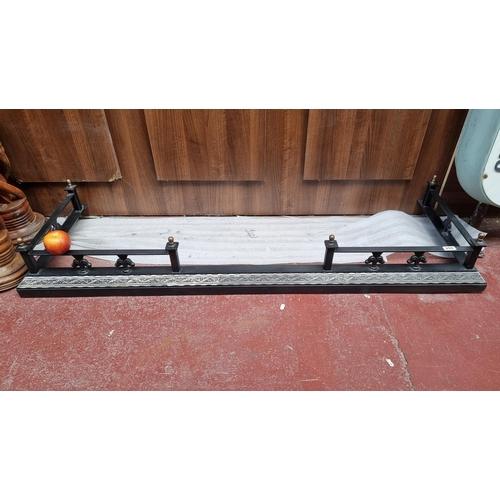 259 - A heavy black metal fire fender with rail and steel decorative panel depicting fern motif. L160cm X ...