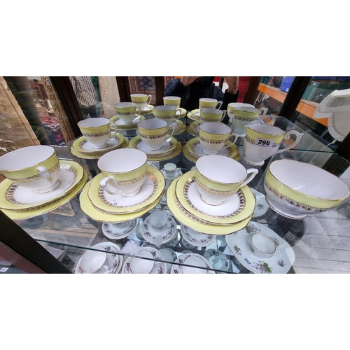 296 - 20 pieces of Queen Anne Bone China with a yellow rim and floral border.