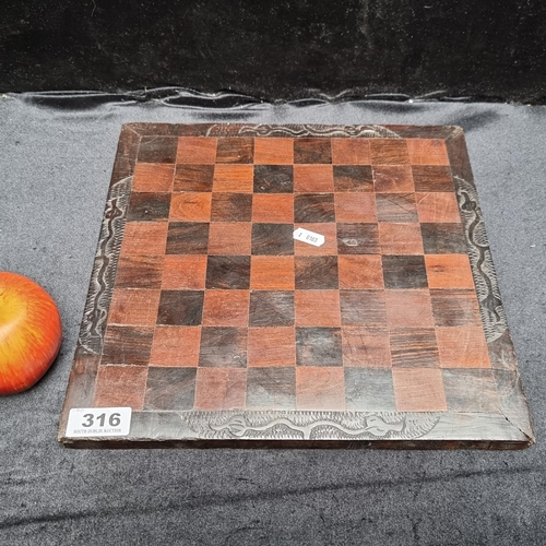 316 - Wooden inlay African chessboard with hand engraved foliate boarder.