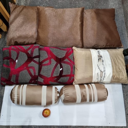 561 - A selection of 8 throw cushions, beautifully upholstered in shades of rich brown, mauve and fuchsia....