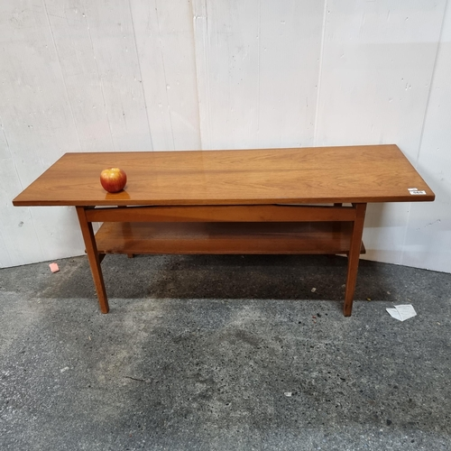 565 - A mid century modern  coffee table with curved side panel detailing, gently tapering legs and shelf ...