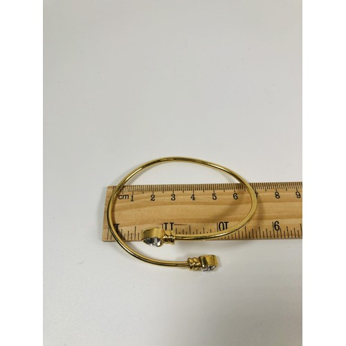 48 - Gold bangle with stone set heart end detail. Tests as 9ct. 12.35gr...
