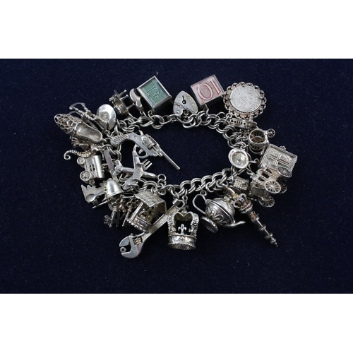 26 - Silver charm bracelet with charms Assay stamps for London 1975. Stamps both on padlock clasp and end...