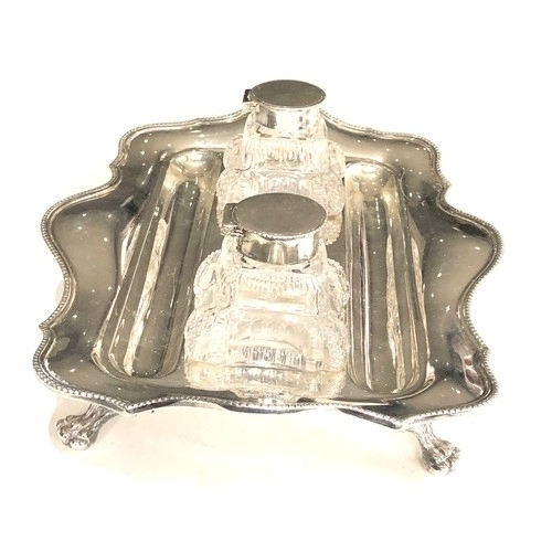 14 - A George V silver shaped rectangular inkstand and  pair of glass inkwells with dished pen rests, bea...